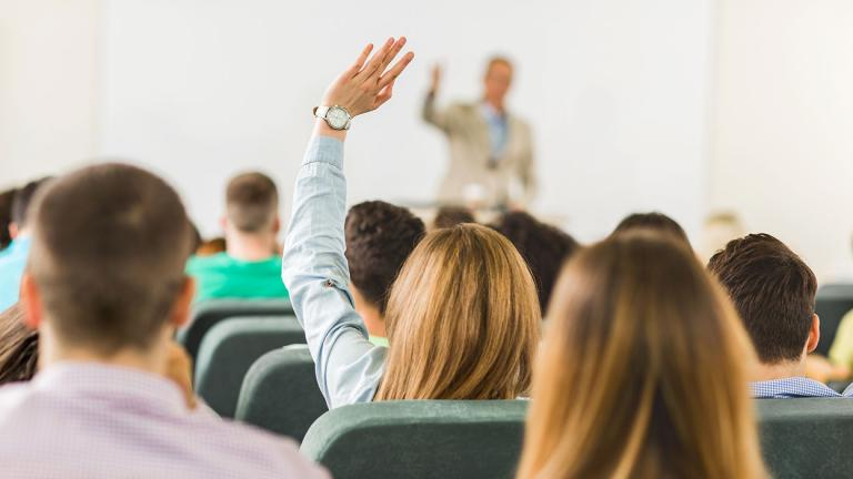 Student raising her hand to ask a question in class