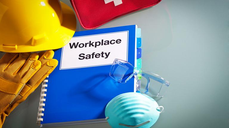 Hard hat, first aid kit, gloves, mask and manual saying workplace safety