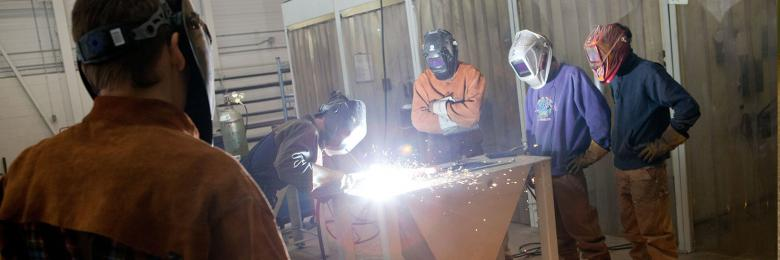 Four men welding on a table