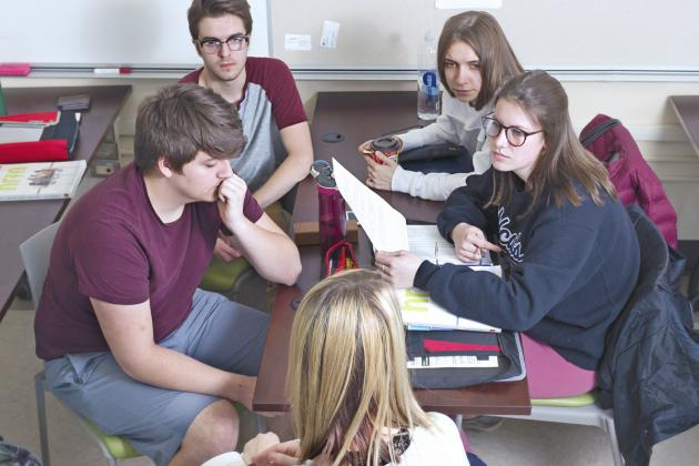 Group of students discussing at a desk
